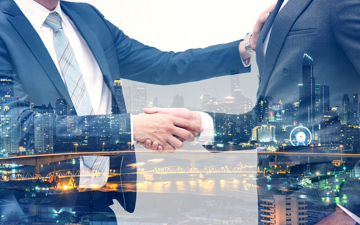 handshake of two people with real estate in background