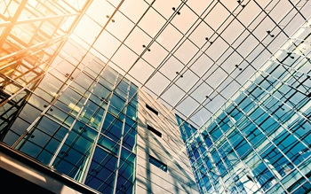 Large glass office building, photograph of glass ceiling with sun shining through.