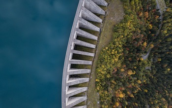 Ariel shot of a large water dam on left, with green trees beneath on the right