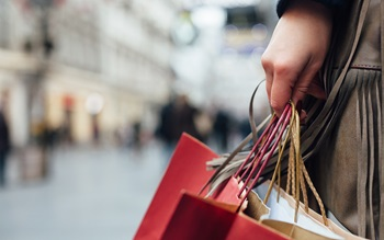image of shopping bags in a female hand with high street in the background