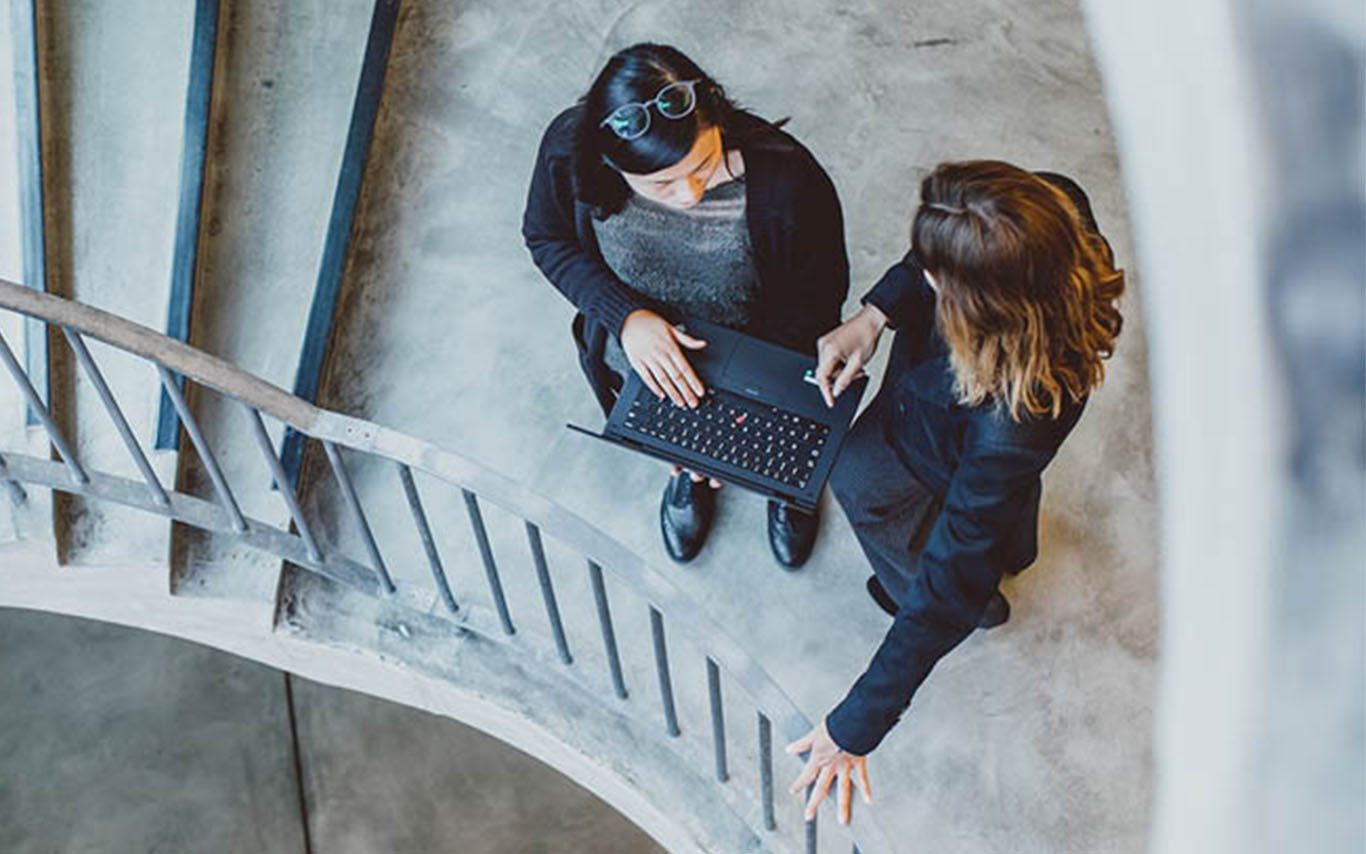 Two colleagues standing on a stair case talking, one holding laptop.