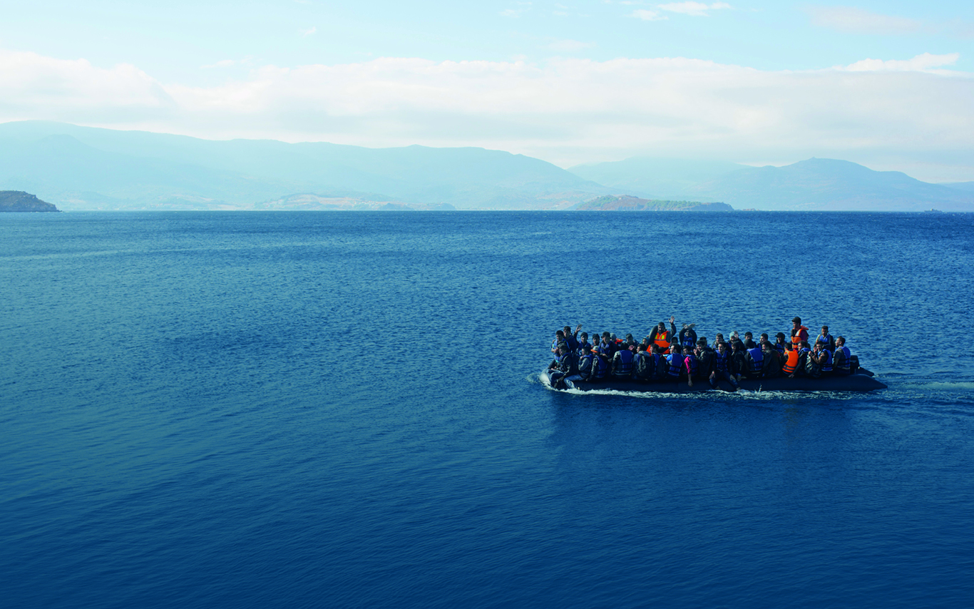 A large group of people at sea on a small boat