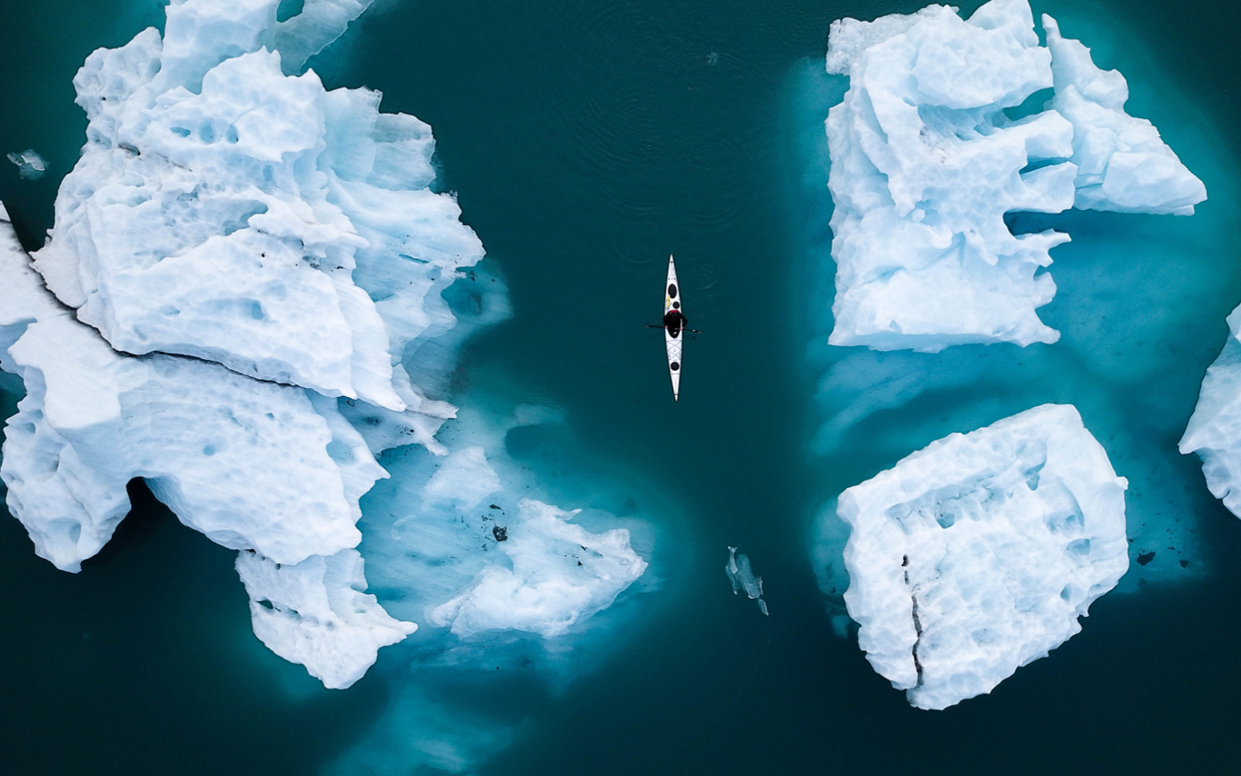 Aerial shot - several ice bergs in blue water with small canoe floating in the middle
