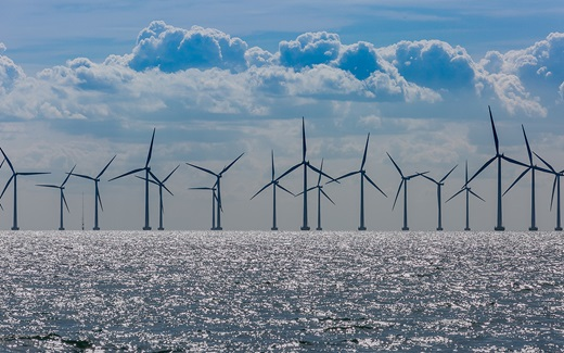 Offshore wind turbines against a blue cloudy sky
