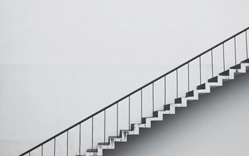 A metal staircase against a white concrete wall