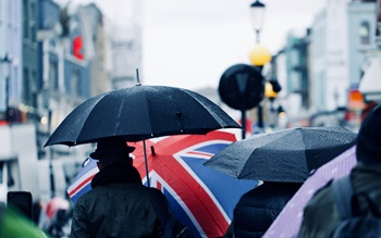 Image of crowded street with union jack umbrella in crowd