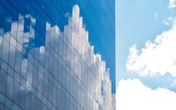 A modern mirrored building reflecting a cloudy blue sky