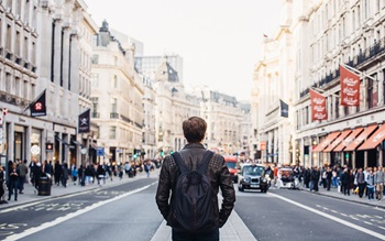 Person facing away from camera looking down a busy street