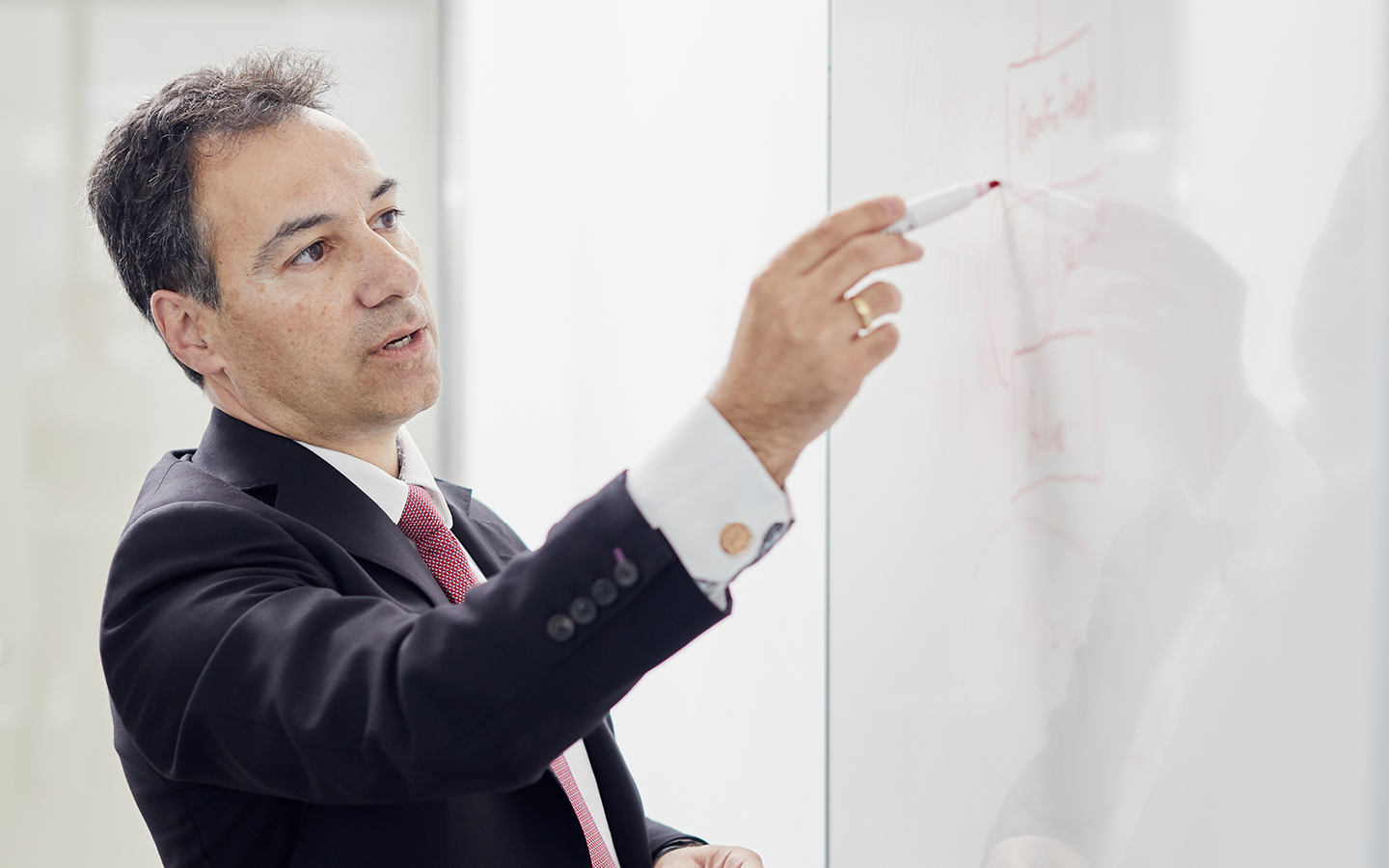 Man with pen pointing at notes written on a whiteboard