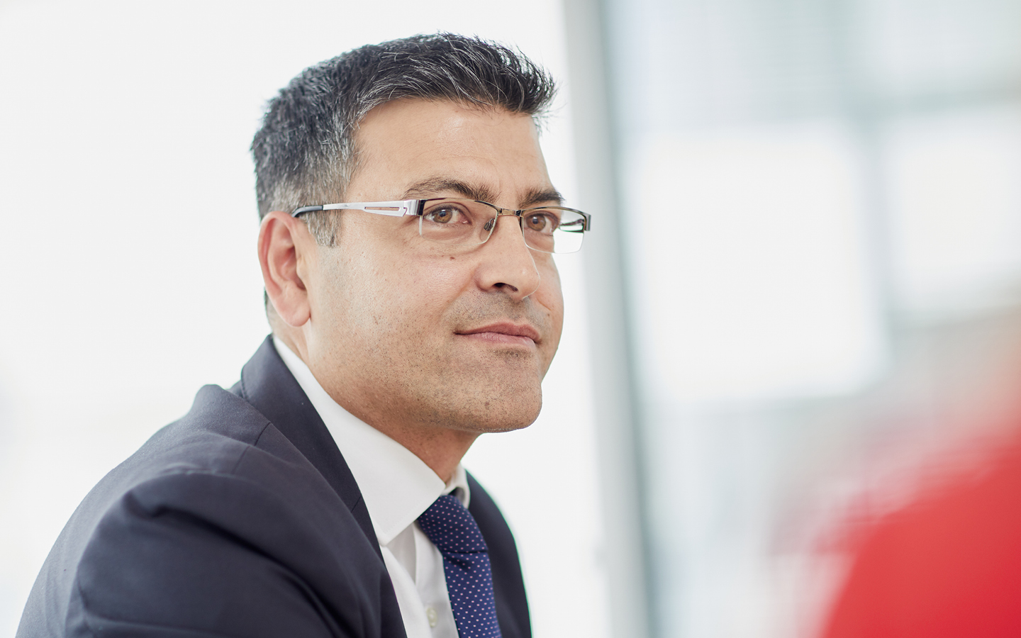 Man with suit and glasses listening to colleague